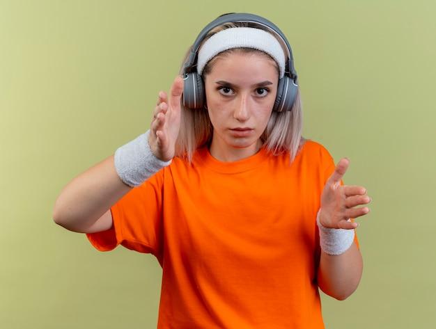 Selbstbewusstes junges kaukasisches sportliches mädchen mit hosenträgern auf kopfhörern mit stirnband und armbändern hält die hände direkt an die kamera