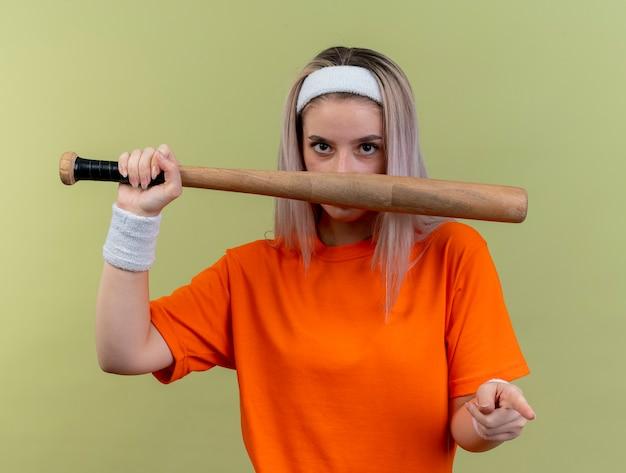 Selbstbewusstes junges kaukasisches sportliches mädchen mit hosenträgern, das stirnband und armbänder trägt, baseballschläger hält und auf die kamera zeigt