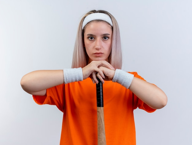 Selbstbewusstes junges kaukasisches sportliches mädchen mit hosenträgern, das stirnband und armbänder trägt, hält baseballschläger auf dem kopf