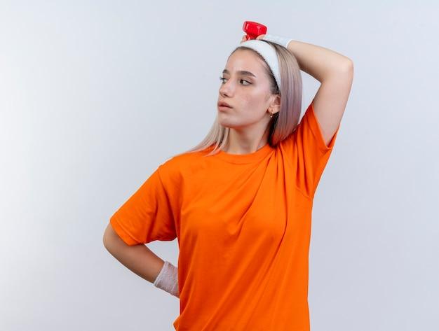 Selbstbewusstes junges kaukasisches sportliches mädchen mit hosenträgern, das stirnband und armbänder trägt, hält hantel hinter dem kopf und schaut auf die seite