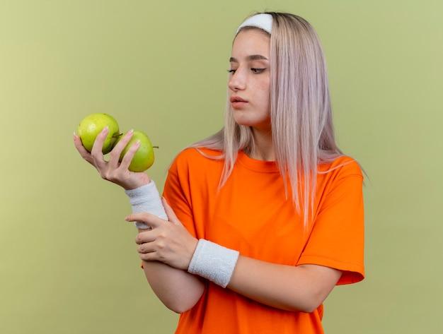 Selbstbewusstes junges kaukasisches sportliches mädchen mit hosenträgern, das stirnband und armbänder trägt, hält und betrachtet äpfel
