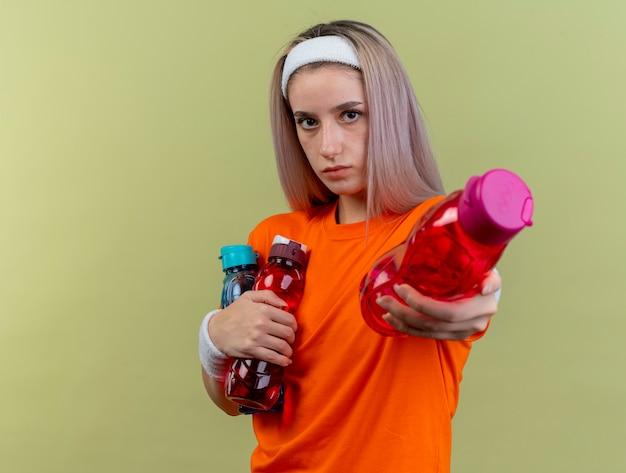Selbstbewusstes junges kaukasisches sportliches mädchen mit hosenträgern, das stirnband und armbänder trägt, hält wasserflaschen mit blick auf die kamera