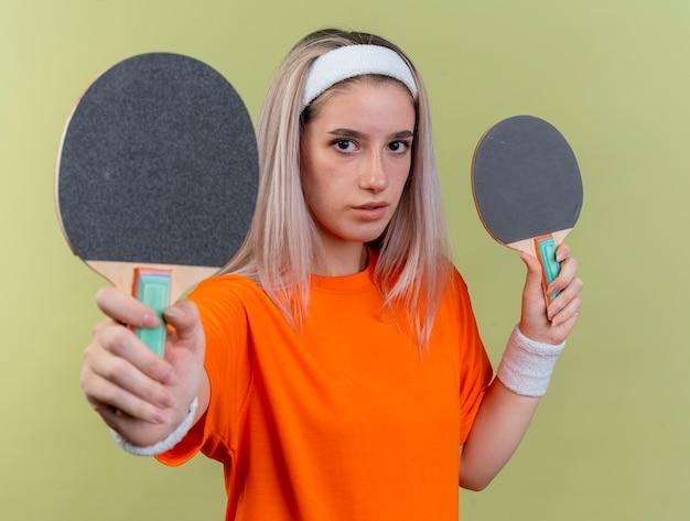 Selbstbewusstes junges kaukasisches sportliches mädchen mit hosenträgern, das stirnband und armbänder trägt und tischtennisschläger hält