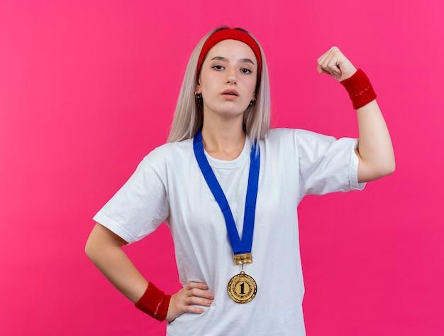 Selbstbewusstes junges kaukasisches sportliches mädchen mit hosenträgern und mit goldmedaille um den hals, das stirnband und armbänder trägt, spannt den bizeps an