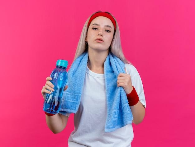 Selbstbewusstes junges kaukasisches sportliches mädchen mit hosenträgern und mit handtuch um den hals, das stirnband und armbänder mit wasserflasche trägt