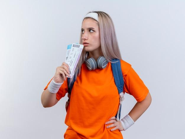 Selbstbewusstes junges kaukasisches sportliches mädchen mit kopfhörern um den hals, das rucksackstirnband und armbänder trägt, hält flugtickets auf der seite