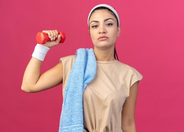 Selbstbewusstes junges kaukasisches sportliches mädchen mit stirnband und armbändern, das hantel mit handtuch auf der schulter anhebt und auf die vorderseite isoliert auf rosa wand schaut
