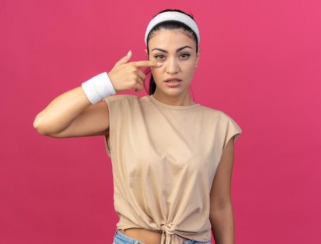 Selbstbewusstes junges, kaukasisches, sportliches mädchen mit stirnband und armbändern, das nach vorne schaut und den finger unter das auge legt, isoliert auf rosa wand mit kopierraum Premium Fotos