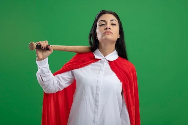 Selbstbewusstes junges kaukasisches superheldenmädchen, das baseballschläger auf ihrer schulter hält und kamera lokalisiert auf grünem hintergrund betrachtet