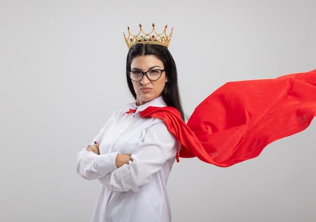 Selbstbewusstes junges kaukasisches superheldenmädchen, das brille und krone trägt, die mit geschlossener haltung in der profilansicht stehen, die kamera lokalisiert auf weißem hintergrund mit kopienraum betrachtet