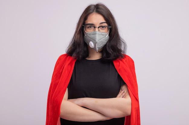 Selbstbewusstes junges kaukasisches superheldenmädchen im roten umhang mit brille und schutzmaske