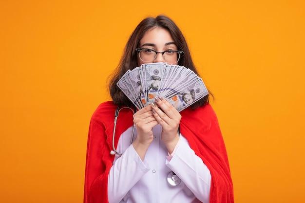 Selbstbewusstes junges kaukasisches superheldenmädchen in arztuniform und stethoskop mit brille, das geld von hinten hält, isoliert an der wand mit kopierraum