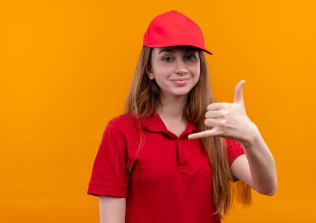 Selbstbewusstes junges liefermädchen in der roten uniform, die anrufgeste auf lokalisiertem orange raum mit kopienraum tut