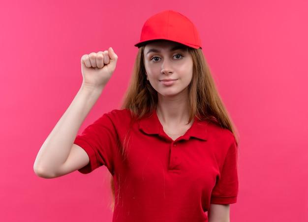 Selbstbewusstes junges liefermädchen in der roten uniform, die klopfgeste auf lokalisiertem rosa raum tut