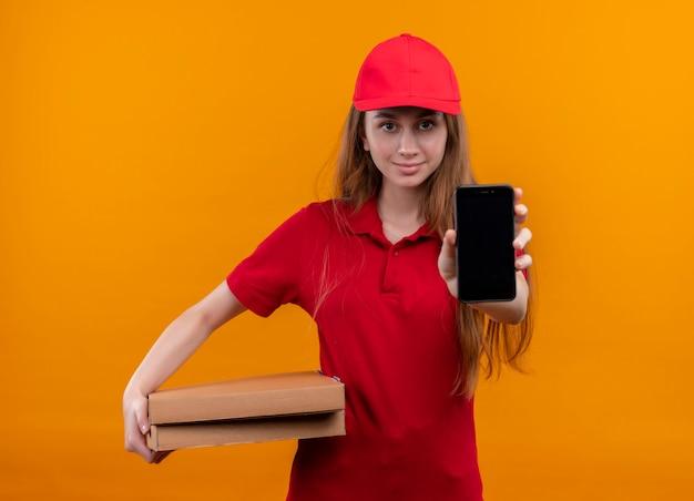 Selbstbewusstes junges liefermädchen in der roten uniform, die paket hält und handy auf isoliertem orange raum ausdehnt