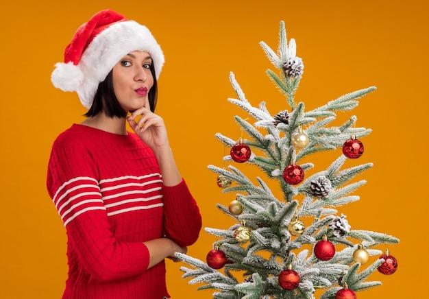 Selbstbewusstes junges mädchen, das weihnachtsmütze trägt, die in der profilansicht nahe verziertem weihnachtsbaum steht und kamera betrachtet, die hand auf kinn lokalisiert auf orange hintergrund hält