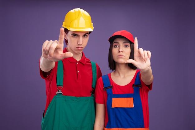 Selbstbewusstes junges paar in bauarbeiteruniform, das einen schutzhelm trägt, das eine mütze trägt, die die hand ausstreckt und eine verlierergeste macht