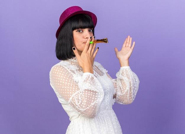 Selbstbewusstes junges partymädchen mit partyhut, das in der profilansicht steht und das partyhorn zeigt, das leere hand einzeln auf lila wand mit kopienraum zeigt