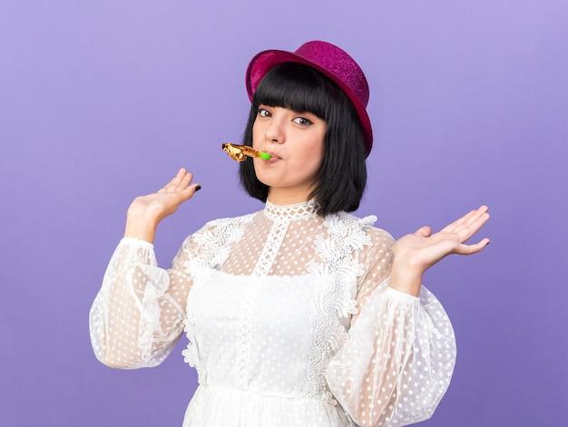 Selbstbewusstes junges partymädchen mit partyhut, das partyhorn bläst, das leere hände isoliert auf lila wand zeigt