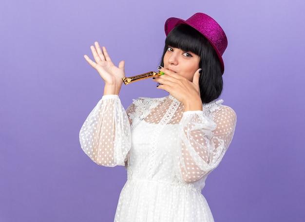 Selbstbewusstes junges partymädchen mit partyhut, das partyhorn bläst, das leere hand isoliert auf lila wand zeigt