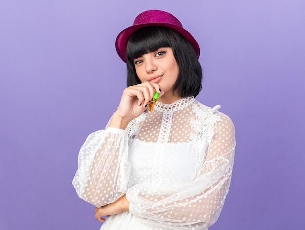 Selbstbewusstes junges partymädchen mit partyhut, das partyhorn isoliert auf lila wand hält