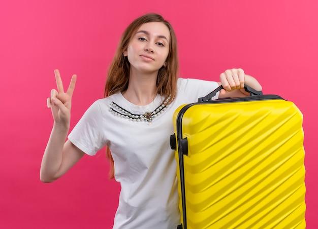 Selbstbewusstes junges reisendes mädchen, das koffer hält, der friedenszeichen auf lokalisiertem rosa raum tut