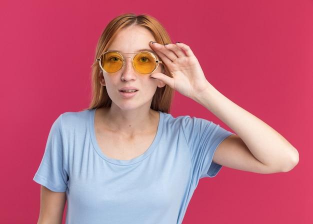Selbstbewusstes junges rothaariges ingwermädchen mit sommersprossen schaut durch eine sonnenbrille in die kamera