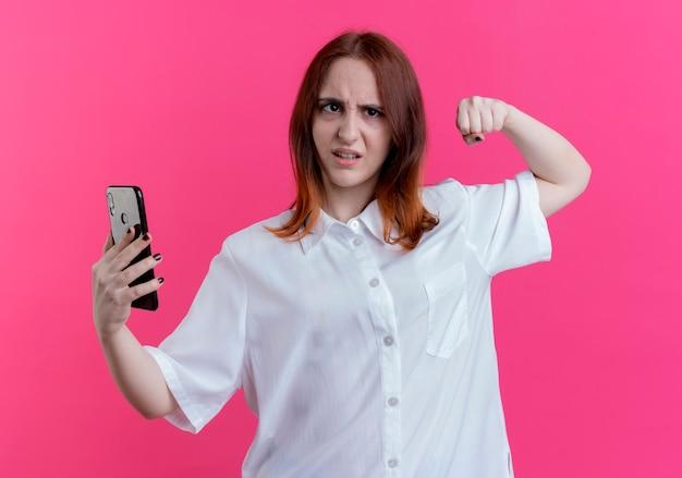 Selbstbewusstes junges rothaariges mädchen, das telefon hält und starke geste zeigt, die auf rosa wand lokalisiert wird