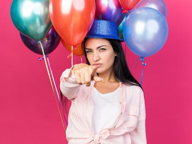 Selbstbewusstes junges, schönes mädchen mit partyhut, das vor ballons steht und ihnen geste einzeln auf rosa wand zeigt