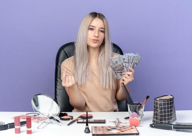 Selbstbewusstes junges schönes mädchen sitzt am tisch mit make-up-tools, die bargeld halten und trinkgeld-geste einzeln auf blauer wand zeigen