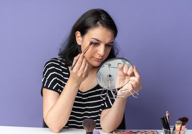 Selbstbewusstes junges schönes mädchen sitzt am tisch mit make-up-tools, die den spiegel halten und betrachten, der lidschatten mit make-up-pinsel auf blauer wand aufträgt
