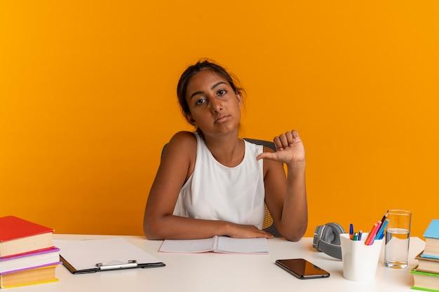 Selbstbewusstes junges schulmädchen, das mit schulwerkzeugen am schreibtisch sitzt, zeigt auf sich
