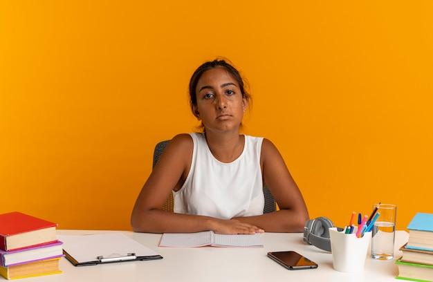 Selbstbewusstes junges schulmädchen, das mit schulwerkzeugen am schreibtisch sitzt