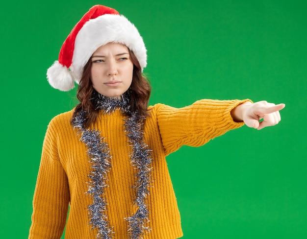 Selbstbewusstes junges slawisches mädchen mit weihnachtsmütze und mit girlande um den hals, die auf grünem hintergrund mit kopierraum lokalisiert und zeigt