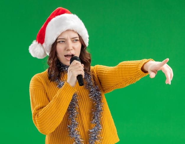 Selbstbewusstes junges slawisches mädchen mit weihnachtsmütze und mit girlande um den hals, die mikrofon hält und zur seite zeigt, lokalisiert auf grünem hintergrund mit kopienraum