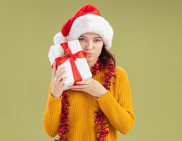 Selbstbewusstes junges slawisches mädchen mit weihnachtsmütze und mit girlande um den hals, die weihnachtsgeschenkbox isoliert auf olivgrüner wand mit kopierraum hält