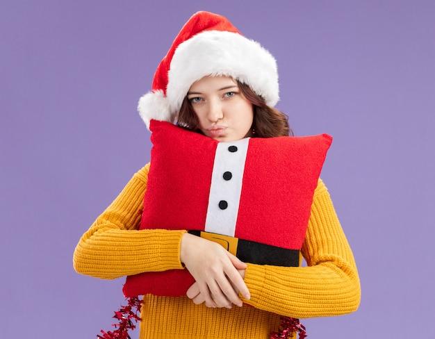 Selbstbewusstes junges slawisches mädchen mit weihnachtsmütze und mit girlande um den hals umarmte dekoriertes kissen, das kamera lokalisiert auf lila hintergrund mit kopienraum betrachtet