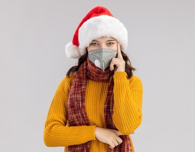 Selbstbewusstes junges slawisches mädchen mit weihnachtsmütze und mit schal um den hals, das eine medizinische maske trägt, legt den finger auf den tempel, isoliert auf weißer wand mit kopierraum