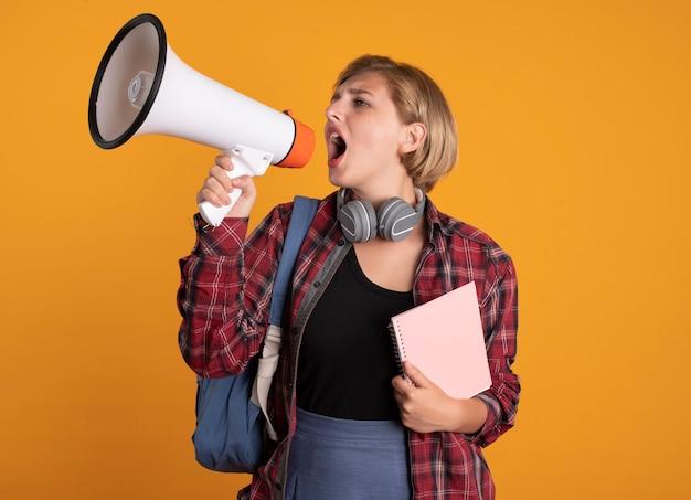 Selbstbewusstes junges slawisches studentenmädchen mit kopfhörern, das rucksack trägt, hält notebook und schreit in den lautsprecher, der auf die seite schaut
