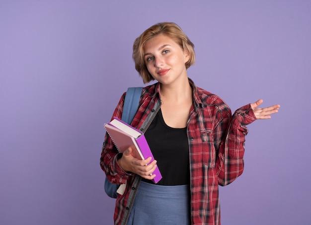Selbstbewusstes junges slawisches studentenmädchen mit rucksack hält buch und notizbuch hält die hand offen