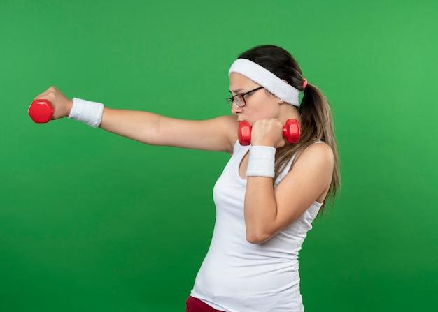 Selbstbewusstes junges sportliches mädchen in optischer brille mit stirnband und armbändern hält hanteln