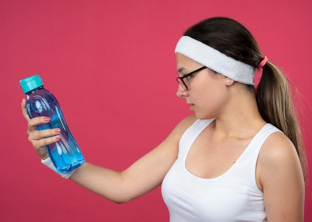 Selbstbewusstes junges sportliches mädchen in optischer brille mit stirnband und armbändern hält und sieht wasserflasche an
