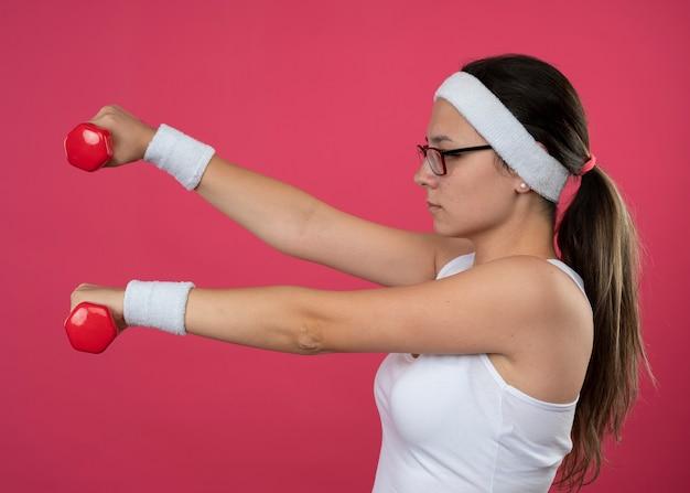 Selbstbewusstes junges sportliches mädchen in optischer brille mit stirnband und armbändern steht seitlich und hält hanteln