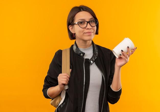 Selbstbewusstes junges studentenmädchen, das brille und rückentasche hält kaffeetasse lokalisiert auf orange mit kopienraum