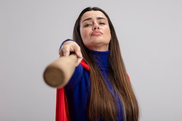 Selbstbewusstes junges superheldenmädchen, das baseballschläger an der kamera lokalisiert auf weißem hintergrund heraushält