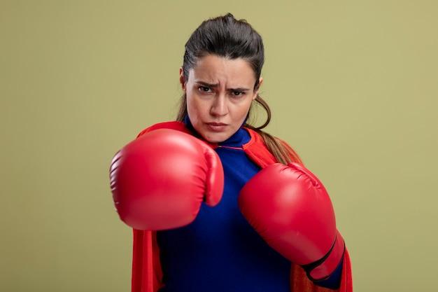 Selbstbewusstes junges superheldenmädchen, das boxhandschuhe trägt, die hand an der kamera lokalisiert auf olivgrünem hintergrund halten