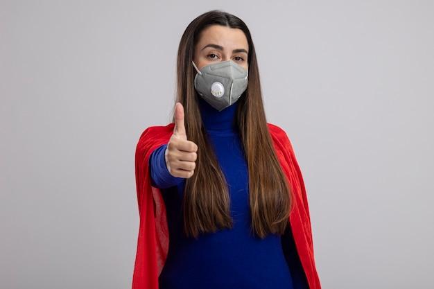 Selbstbewusstes junges superheldenmädchen, das medizinische maske trägt, zeigt daumen oben lokalisiert auf weiß