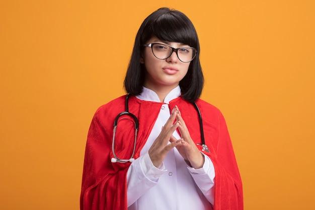 Selbstbewusstes junges superheldenmädchen, das stethoskop mit medizinischem gewand und umhang mit brille trägt, die hände zusammenhalten