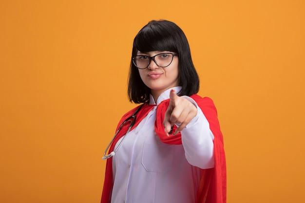 Selbstbewusstes junges superheldenmädchen, das stethoskop mit medizinischem gewand und umhang mit brille trägt, die sie geste lokalisiert auf orange wand zeigt