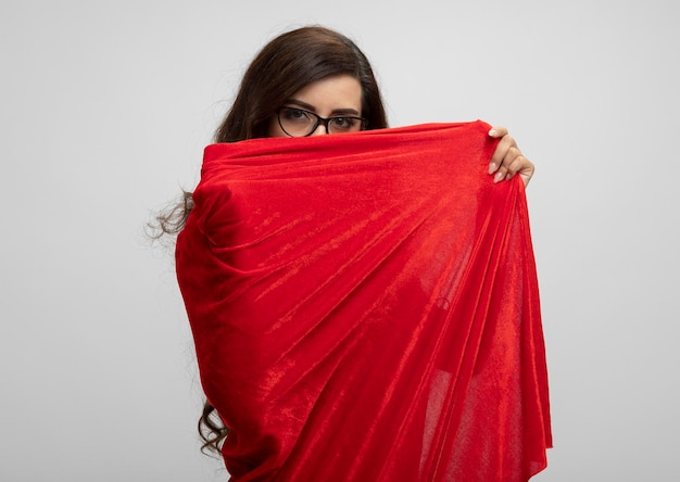 Selbstbewusstes kaukasisches superheldenmädchen in der optischen brille hält und schaut kamera über rotem umhang